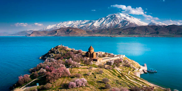 Panoramic view of Armenian Holy Cross Cathedral surrounded by trees in blossom, Akdamr Adasi, Lake Van, Gevas, Eastern Turkey