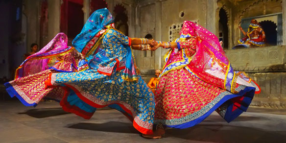 Young indian women in national costumes dance at the open festival, Udaipur, Rajasthan, India